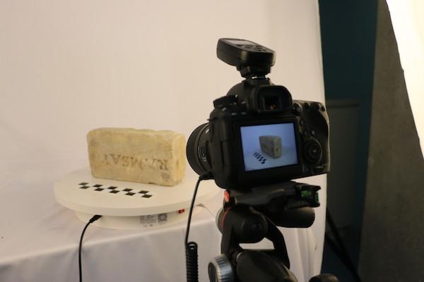 A camera 3D scans a brick