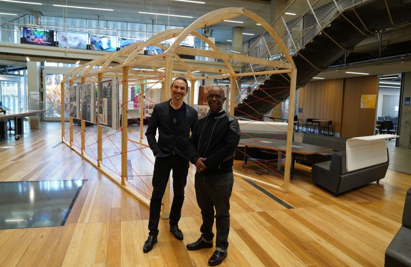 Jefa Greenaway and Mphethi Morojele in front of the Indigenize Montreal exhibition in the Atrium at Melbourne School of Design